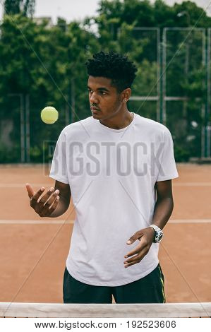 Handsome black guy in polo throws up a tennis ball on the court. Portrait of serious african man looking away.