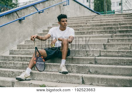 Confident young man in sports clothes on concrete steps. Man holding tennis racket and looking away while sits against grey background.