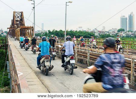 Hanoi, Vietnam - May 24, 2017: People On Motorbikes Crossing The  Long Bien Bridge In Hanoi, Which C