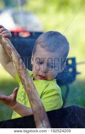 Cute little boy chopping kindling to start a fire using a stick concentrating carefully on what he is doing.