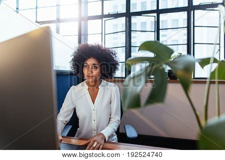 Indoor shot of young african woman sitting at her desk and working on computer. Female executive working in office.
