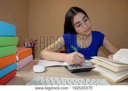 Young Girl studying. Girl doing her homework. School books on desk education concept