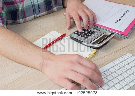 Businessman hand holding ballpoint pen working on computer working online concept e business concept