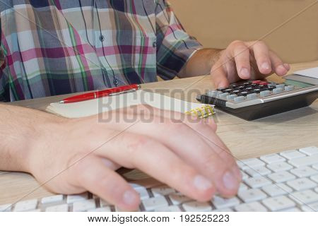 Man hands with pencil notebook and Calculator on wooden table. The Man are using a calculator on the table in the office room
