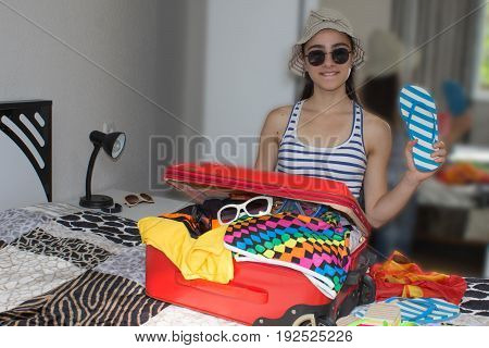 Happy young woman in colorful summer outfit sitting near the red staffed suitcase smiling. Travel concept
