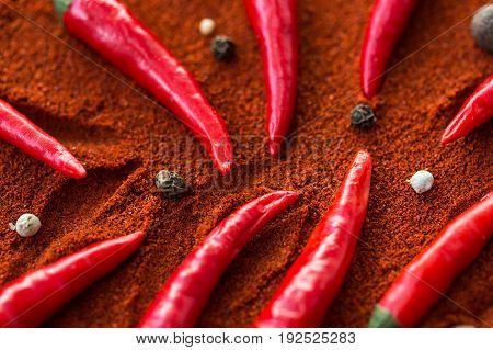 red hot chili peppers, popular spices concept - close-up on beautifully designed red chili peppers on a brown background of ground dried pepper with round black seeds and white pepper