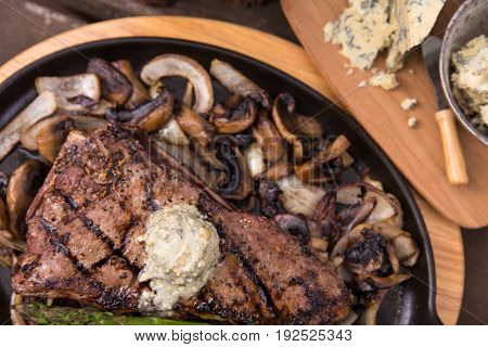 delicious grilled steak shown from above on a cast iron skillet surrounded by fried onions and mushrooms and topped with blue cheese steak butter