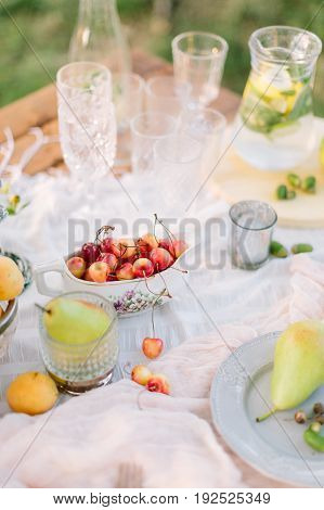 picnic, food, summer, holiday concept - close-up on wooden festive table with white tablecloth, dish with cherries, served with glass cups, goblets, glasses, fruit plates, pitcher of lemonade.