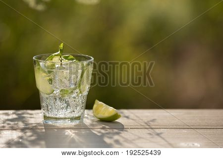 A glass of soda water on an old board on nature ice bubbles grapefruit spike
