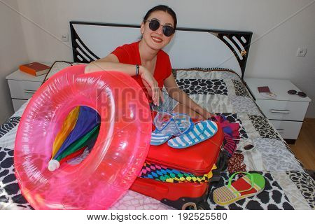 Happy young woman in colorful summer outfit sitting near the red staffed suitcase smiling. Female Getting Ready For Traveling