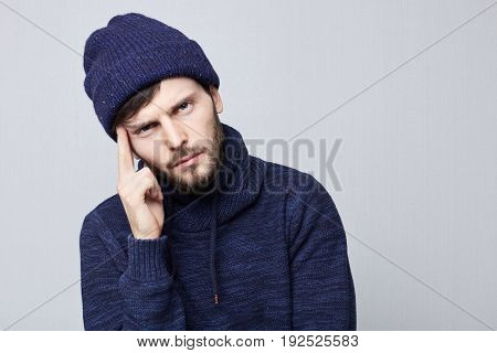 Horizontal shot of unhappy and upset young Caucasian hipster employee or customer having thoughtful pensive expression looking at camera in frustration keeping finger on his temple feeling exhausted