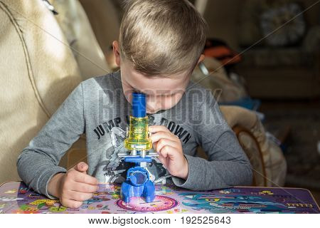 Sochi, Russia - 13 May, 2017. Little kid conducts experiment with microscope at home.