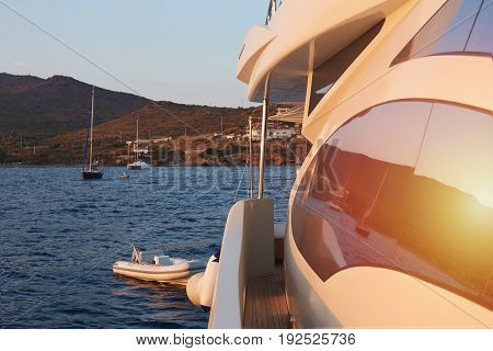 Picturesque reflection of sunset on luxury modern yacht sailing in the sea and coming to the shore. Marine scene of gorgeous sunset.