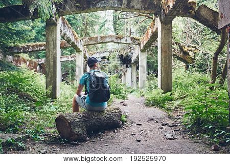 Young explorer inside of the abandoned old ruined factory in the middle of the forest. Ore mountains Czech Republic