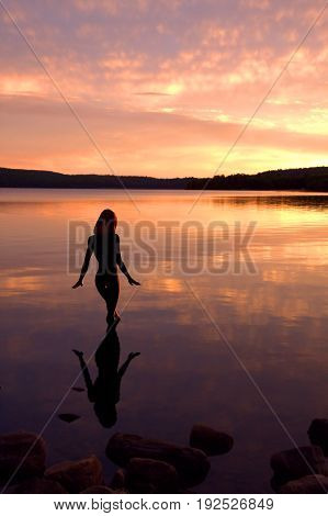 Young woman cautiously steps into the cool waters of a lake