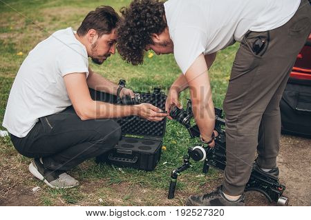 Behind The Scene. Cameraman And Assistant Changes Lens On Camera