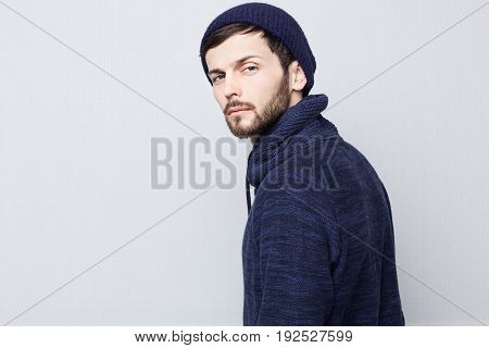 Sideways portrait of natural brunette Caucasian man wearing warm clothes on white background. Bearded hipster with clean shaved temples and stylish well-trimmed moustaches looking serious and brutal at the camera.