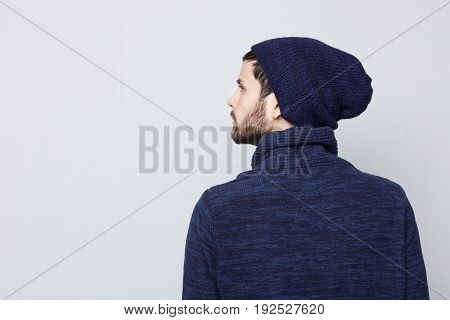 Sideways portrait of natural brunette Caucasian man wearing warm clothes on white background. Bearded hipster with clean shaved temples and stylish well-trimmed moustaches looking serious and brutal to the area of copy space.