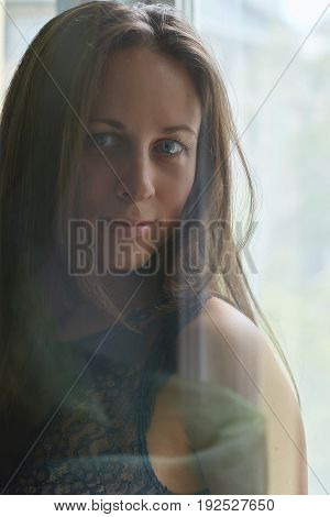 Shot through the glass. Close up portrait of happy Caucasian woman with blue eyes smiling and looking at the camera posing in front of the window background.