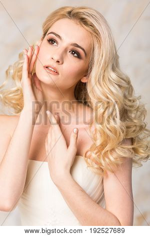 fashionable gown, beautiful blonde model, bride hairstyle and makeup concept - closeup on young pretty romantic lady in white festive wedding dress, slender woman indoor on a light background