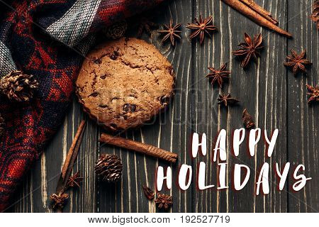 Happy Holidays Text Sign On Cookie Anise Cinnamon And Pine Cones On Wooden Background, Stylish Rusti