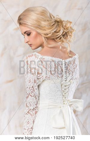 fashionable gown, beautiful blonde model, bride hairstyle and makeup concept - young romantic lady in white wedding dress, pretty slender woman stand indoors on light background, back view