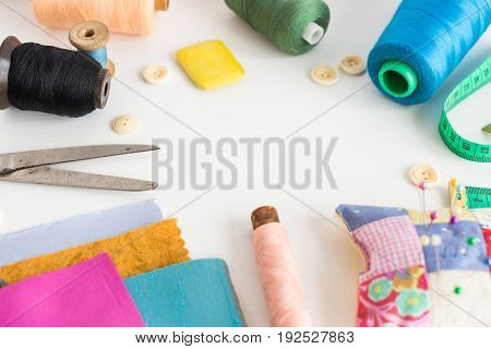 tailoring and fashion concept, patchwork, close sewing tools - working environment on a white table, thread spools, buttons, meter, pincushion, scissors, pieces of colored patchwork fabric, soap