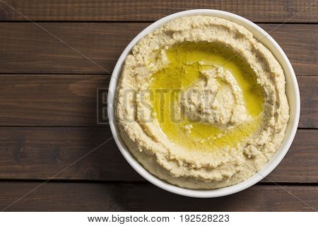 Hummus in a white dish on wooden background