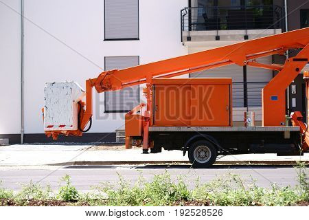 A lifting platform on a small truck stands in front of a modern residential building.