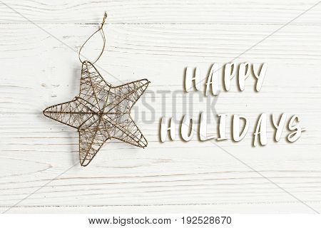 Happy Holidays Text Sign On Christmas Golden Star On Stylish White Rustic Wooden Background. Space F