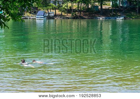 Two teens casually swimming and exploring in a lake in Virginia