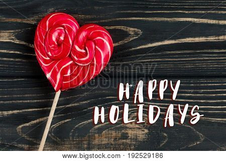 Happy Holidays Text Sign On Heart Candy Lollipop On Stylish Black Rustic Wooden Background. Space Fo