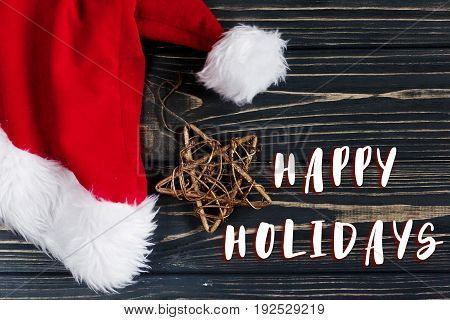 Happy Holidays Text Sign On Christmas Golden Star And Santa Hat On Stylish Black Rustic Wooden Backg