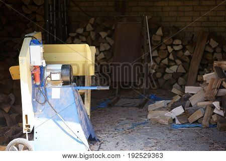 The front view of a wood saw in a room with firewood.