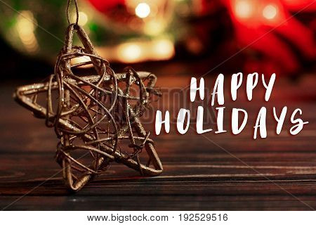 Happy Holidays Text Sign On Christmas Golden Star On Background Of Garland Lights On Black Rustic Wo