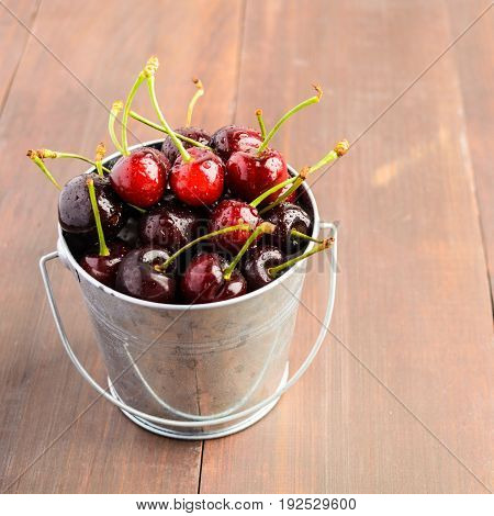 A Bucket Full Of Cherry Over Wooden Background