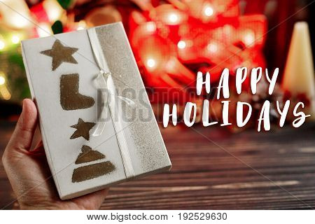 Happy Holidays Text Sign On Hand Holding Christmas Wrapped Present Box On Background Of Warm Garland