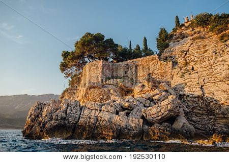 Rocky coast of the Adriatic Sea in Montenegro at sunset, view from the sea
