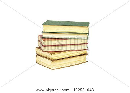 Hard-bound book lie on top of each other on a light surface