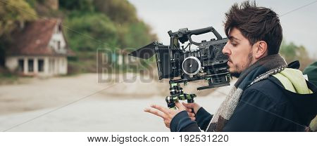 Behind the scene. Cameraman shooting the film scene with his camera on outdoor location poster