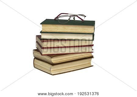On a white surface is a pile of book and reading glasses