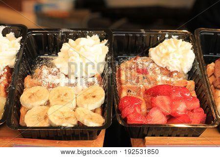 Fresh made Belgium waffles with banana or strawberries and cream