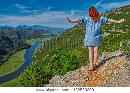 Young woman looking over Majestic Crnojevica River Panorama in Skadar Lake National Park of Montenegro