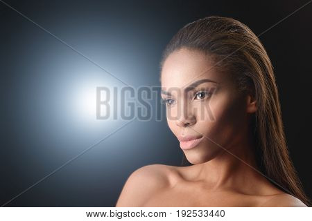 Portrait of confident nude mulatto girl standing and looking forward with passion. Bright light is on background. Copy space
