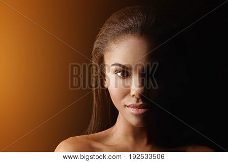 Mysterious nude young mulatto girl is standing with light effect illuminating half of her face. He is looking at camera with confidence. Portrait