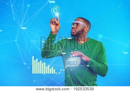 How to make money. Confident young futuristic man drawing graphic on invisible touch board. He is standing and looking at dollar sign with seriousness. Portrait
