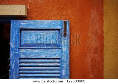 blue wood window with grunge texture on the orange and yellow wall.