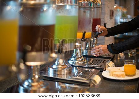 Woman hand pulling down the lever of juice dispenser for fresh orange juice
