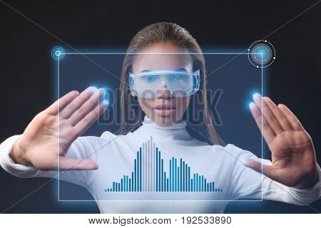 Future technology concept. Self-assured young mulatto businesswoman creating business virtual graphic on touchscreen