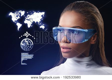 Futuristic social network around the world. Assertive young african girl is looking at map of the earth through special eyewear with interest. Graphic design